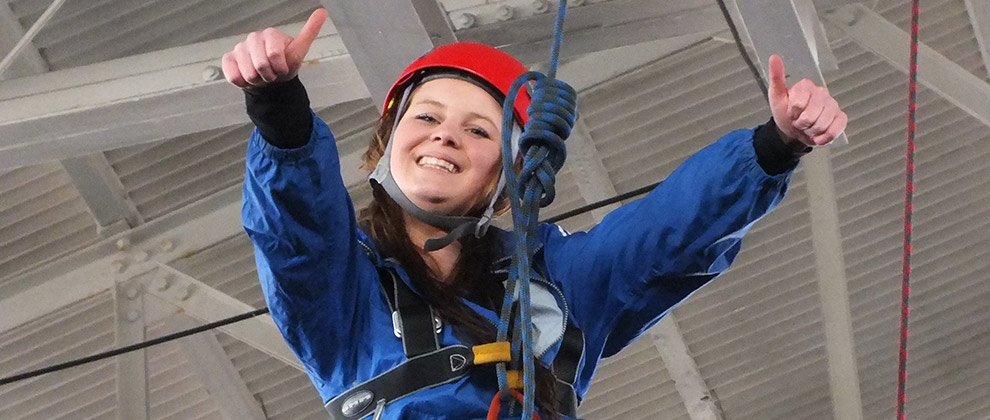 Charlotte from STEPS to 16 enjoying a moment of achievement on a residential activities course.